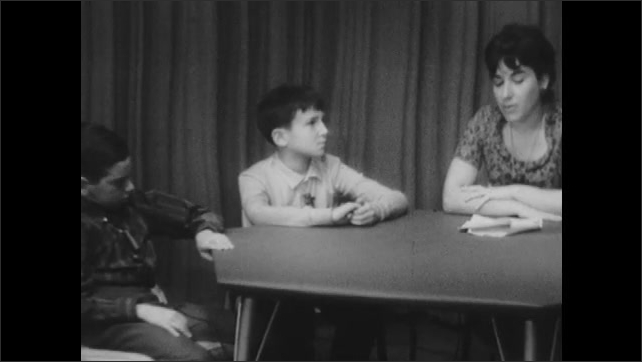 1960s: Woman sits at table and talks to kids.