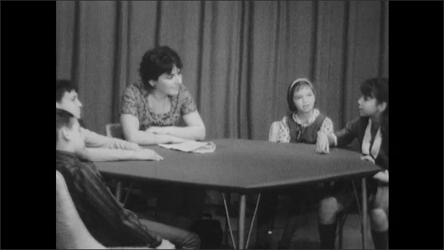 1960s: Woman and kids sit around table and talk.