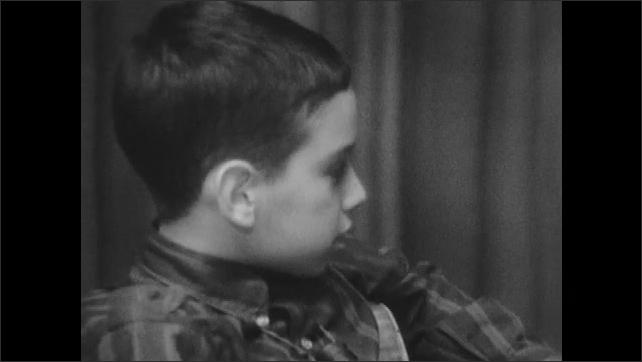 1960s: Little boy talks. Woman sits at table, talks to kids.