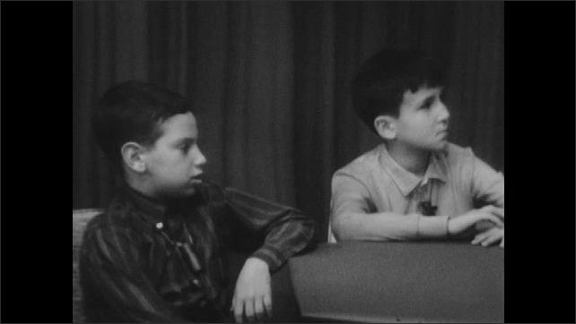 1960s: UNITED STATES: girls listen to lady speak at table. Boys listen to lady talk. Children talk to interviewer.
