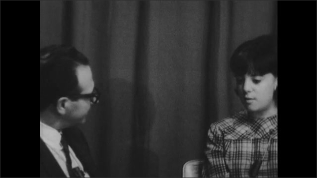 1960s: UNITED STATES: teenager talks to man in interview. Man listens to teenager at table. Man nods head.