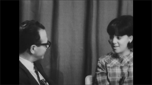 1960s: UNITED STATES: man listens to teenager speak in interview. Girl speaks to interviewer. Teenager answers questions in meeting