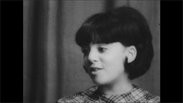 1960s: UNITED STATES: man asks teenager questions in interview. Girl answers questions in interview. Girl smiles.