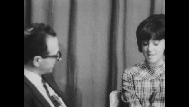 1960s: UNITED STATES: teenager talks to man in interview. Girl listens to questions. Man talks to girl. Girl smiles at man.