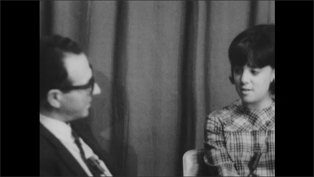 1960s: UNITED STATES: man nods head at teenager. Girl smiles at man in interview. Interviewer speaks to girl.