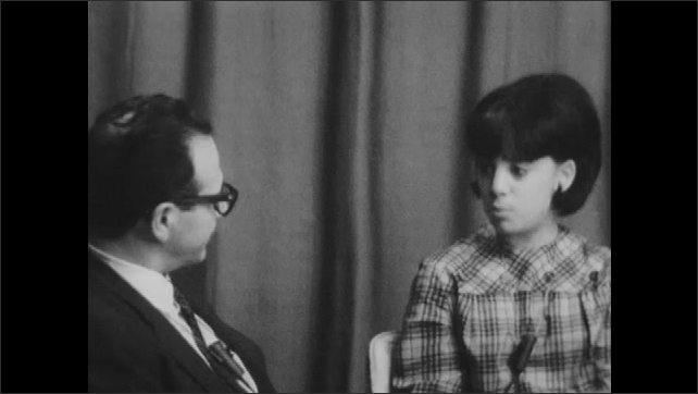1960s: UNITED STATES: man nods head as girl speaks. Girl answers interview question. Girl smiles in interview