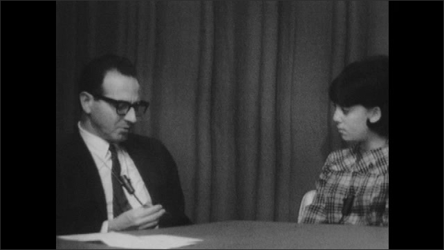 1960s: UNITED STATES: man laughs in interview. Man reads question from sheet. Man interviews teenager. Close up of girl's face.