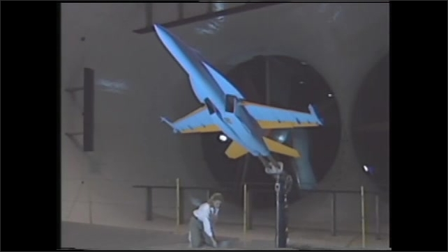 1990s: UNITED STATES: wind tunnel testing of performance before mass scale manufacturing. Men speak in wind tunnel.
