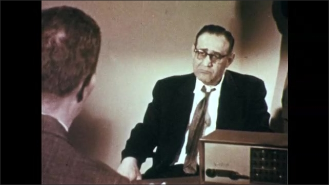1950s: Men sit in office and talk.  Man smokes cigarette.