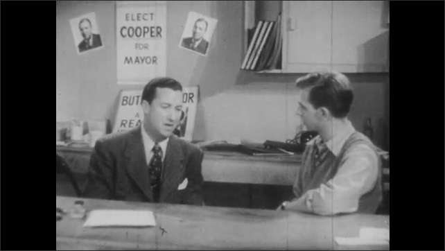 1940s: Newspaper headline says Cooper Re-elected. Two men talk to each other seated behind a table in campaign office.