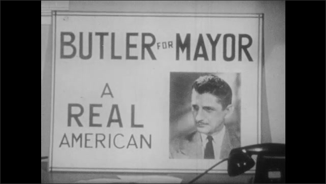 1940s: Two men sit behind a desk in campaign office talking to each other. One man points to poster on wall. Campaign poster, Butler for Mayor. The two men talk while one points to poster.