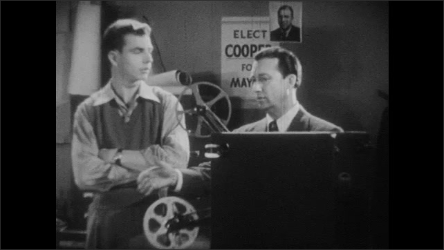 1940s: An older man and a younger man stand behind a film projector, talking. Man plays projector. Woman stands in kitchen, mixing batter in bowl.