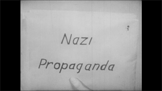1940s: Younger man and older man talk to each other in campaign office. Older man grabs folders from shelf that are labeled: Nazi Propaganda, Russia, Communism, U.S. Elections, High Tariff.