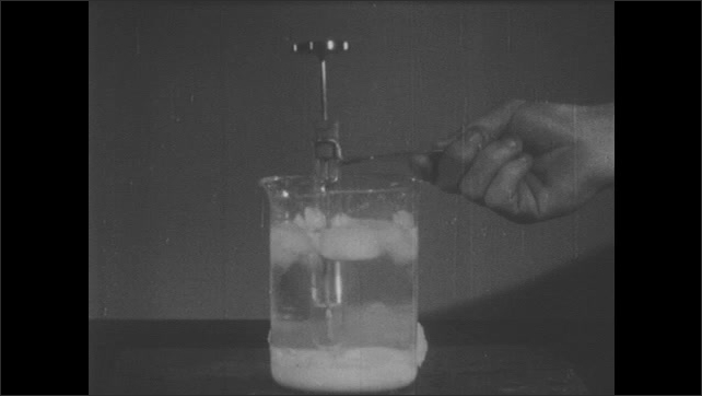 1940s: Person holds test tube of water with thermometer. Icebox door opened, ice inside. Test tube of water inserted into glass of liquid and ice. Test tube of water freezes. Thermometer rises to 0.