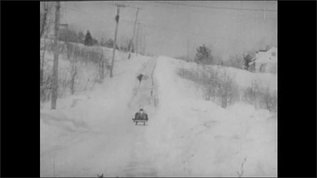 1940s: Dog runs down hill, man and boy sled down hill toward camera.