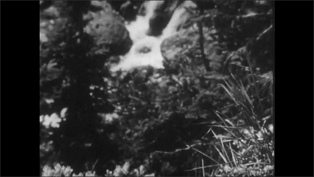 1940s: View of mountain peak. Waterfall in forest. Long shot of people camping next to stream.