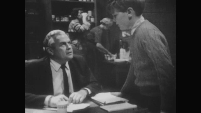 1960s: UNITED STATES: boy talks to man at table. Boy runs off.