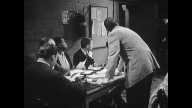 1960s: Man seated at table in Fallout Shelter talks to man standing next to him. Men seated around table. Seated man talks to standing man.