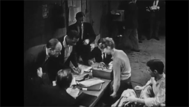 1960s: Man talks with megaphone to people in Fallout Shelter in dark. Man stops talking and lights come on. Woman approaches man and sits at table with men, talking.