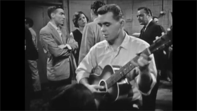 1960s: Man walks through Fallout Shelter then stops. Man walks up to group talking. Man walks by people listening to man play guitar.