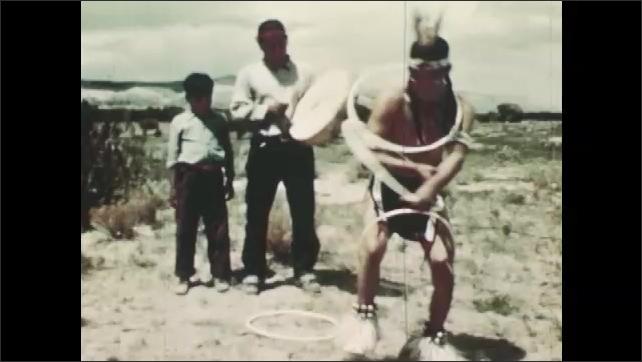1940s: Man plays drum. Man dances hoop dance. Child watches dancer, smiles.