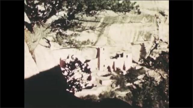 1940s: Native American ruins in mountainside. Man and boy walk through ruins.