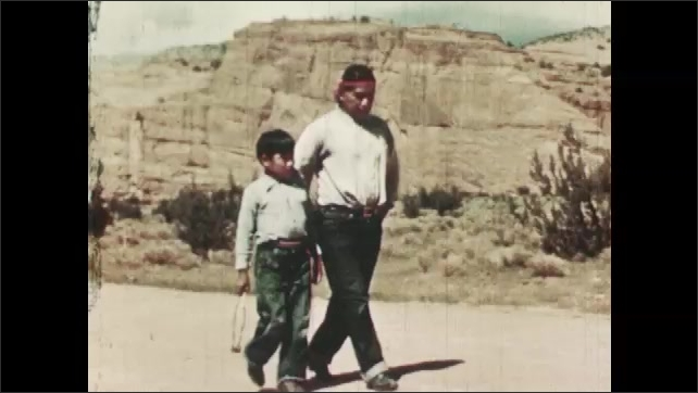 1940s: Man and boy walk down dirt road in the desert.