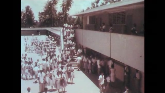 Puerto Rico 1960s: Group of people constructing a building, small cement mixer. Boys and girls in uniform at school courtyard.