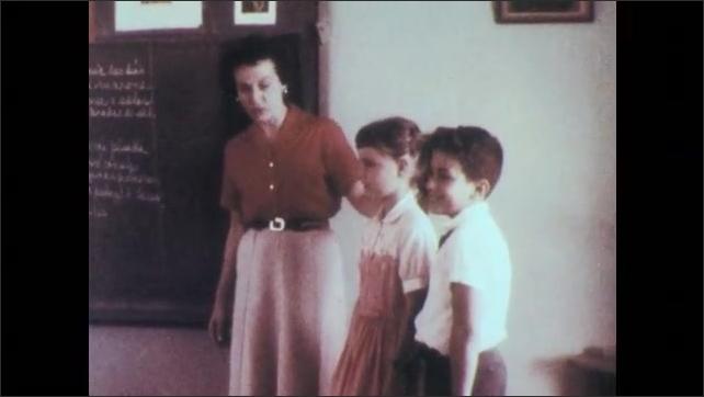 Puerto Rico 1960s: Teacher smiles at boy and girl in classroom. Teacher introduces girl to class.