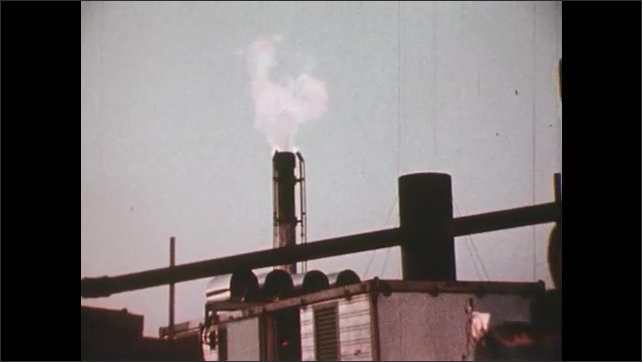 1980s: A man in an office looks up at two computer screens. Steam leaves a chimney at a power plant.