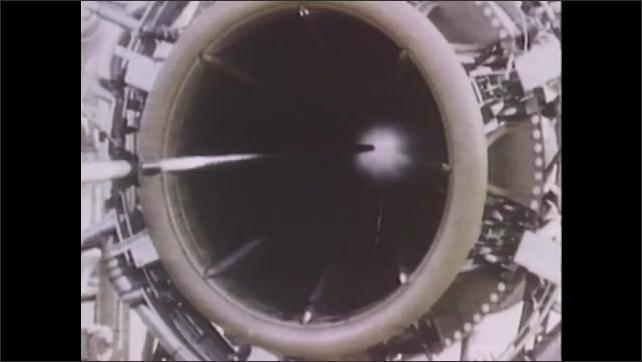 1970s: UNITED STATES: diaphragm built into jet engine. Close up of jet engine and air flow. Noise reduction studies. Man adjust flow on test engine