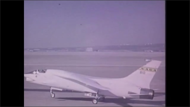 1970s: UNITED STATES: test pilot climbs into plane cockpit. Supercritical wing. Plane takes off from runway
