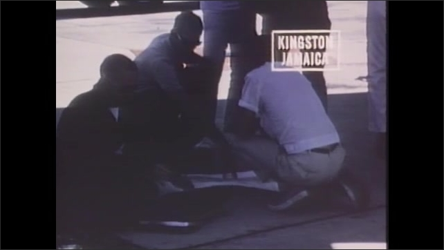 1970s: UNITED STATES: Earth Resources Survey title. Men look at papers under plane. Close up of Jamaica map on ground