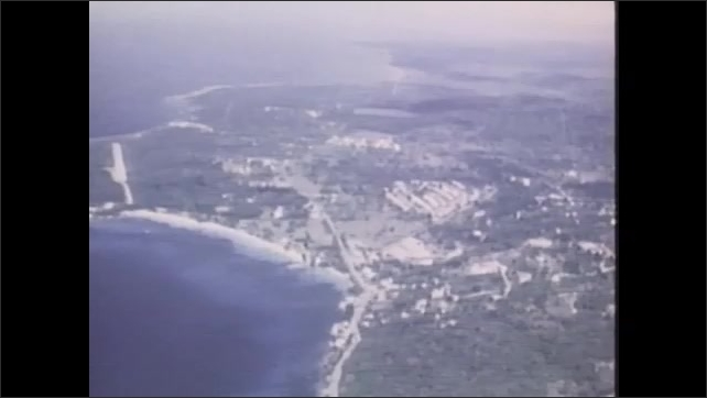 1970s: UNITED STATES: men stand and talk by plane. NASA survey of Jamaica from above.