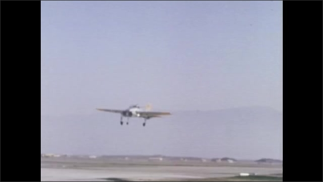 1970s: UNITED STATES: view of runway from X14 plane cockpit. Plane hovers above ground. Plane moves forward and backwards above ground