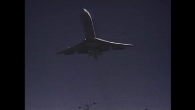 1970s: UNITED STATES: planes takes off from runway. Jets fly over city. Owl on branch at night