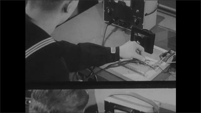 1940s: Voltage meter. Man clips cables onto wire, reads voltage. Man writes on paper.