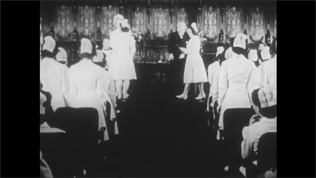 1940s: UNITED STATES: student nurses attend graduation ceremony. Nurses receive diplomas.