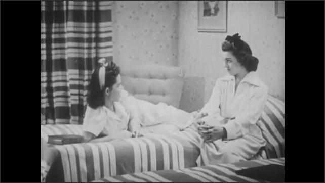 1940s: UNITED STATES: girls sit and talk on bed. Girls enjoy sleepover.