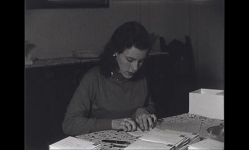1940s: Young woman stuffs and seals envelope.  Woman licks stamp and places on envelope.