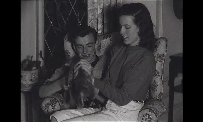 1940s: Young woman sits in young man's lap.  Couple play with kittens.