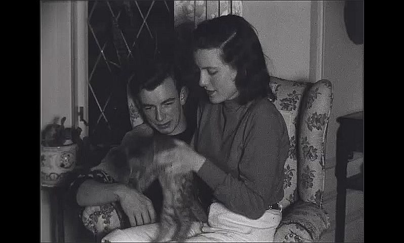 1940s: Young woman sits in young man's lap.  Couple play with kittens.  Woman hands kittens to man.