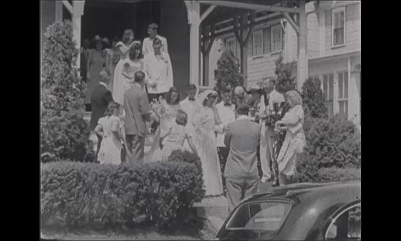 1940s: Wedding.  Photographer.  Bride and groom come out of house.  Bridal party poses on steps.  People throw confetti.