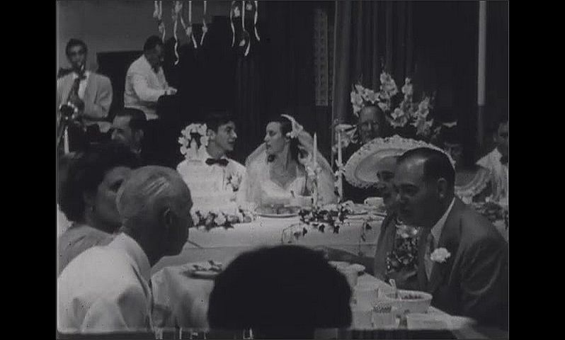 1940s: Wedding reception.  Bride and groom sit between priests at table.