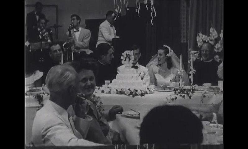 1940s: Wedding reception.  Bride and groom stand and kiss.  People talk.  Band plays.  Woman serves food to bridal party.