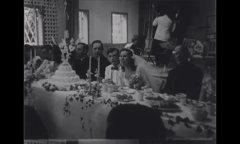 1940s: Wedding reception.  Bridal party sits at head table and eats.