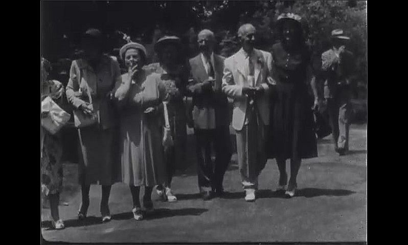 1940s: Wedding reception.  People stroll together outside venue.