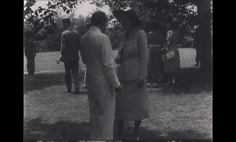 1940s: Wedding reception.  Couple speaks and gestures.  Bride walks past.