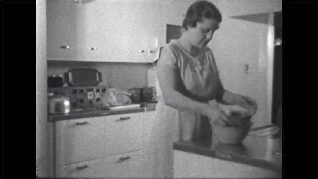 1930s: Woman in the kitchen mixes and stirs while baking.