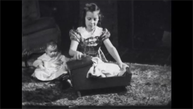 1930s: Little girl winds up a music box on her wooden cradle. The cradle plays Rock-a-Bye Baby as the little girl rocks her baby doll in the cradle.